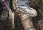 Builder Repairing Sewerage Pipe On Site
