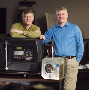 Walter Burgess (left) and William Burgess, VP of Operations, with a digital cinema projector that has been retrofitted to accept laser technology.