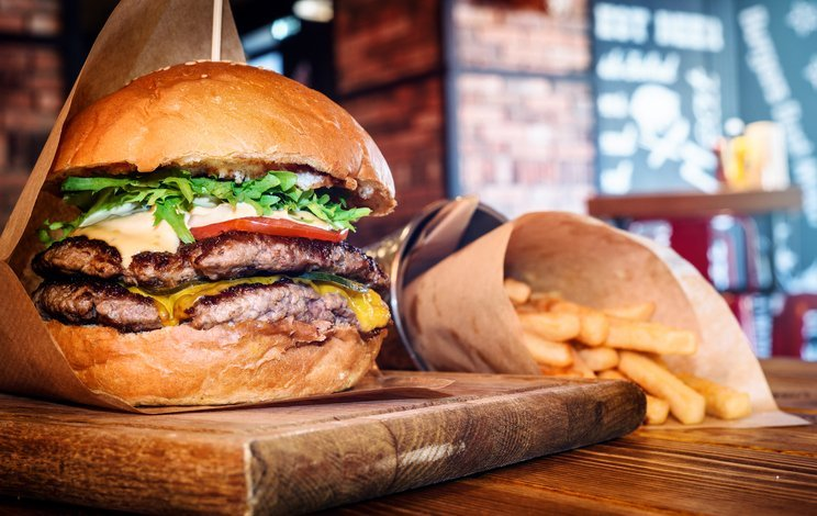 fresh tasty burger and french fries on wooden table at a restaurant