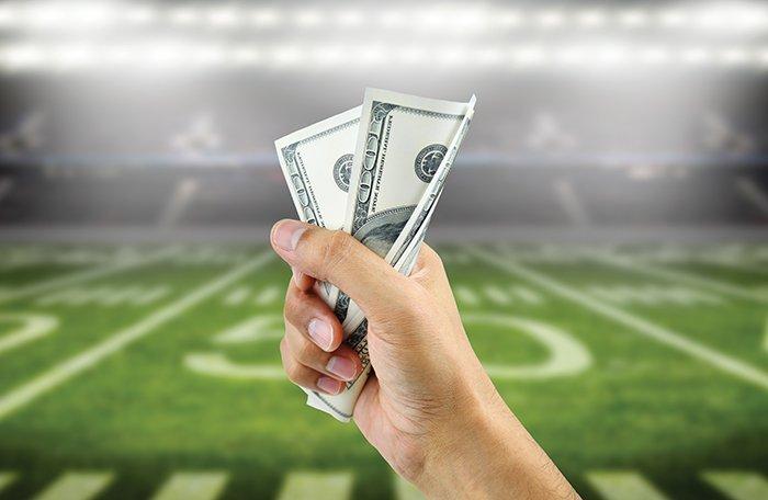 hand holding money football field